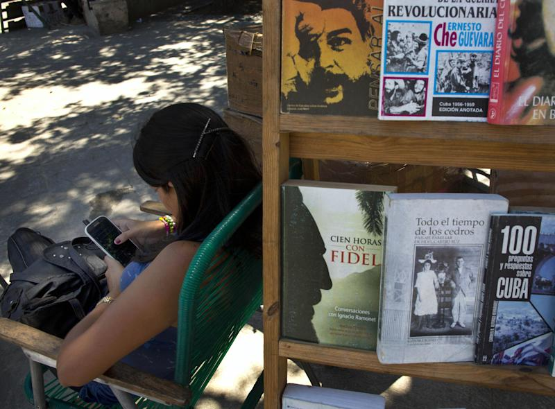 """In this April 1, 2014, photo, a book street vendor passes the time on her smart phone as she waits for customers in Havana, Cuba. The administrator of the U.S. Agency for International Development on Tuesday begins a series of appearances Tuesday, April 8, 2014, before lawmakers asking questions about his agency's secret """"Cuban Twitter,"""" a social media network built to stir unrest in the communist island. First up in the questioning of administrator Rajiv Shah is Sen. Patrick Leahy, D-Vt., who publicly called the social media program """"dumb, dumb, dumb."""" (AP Photo/Ramon Espinosa)"""