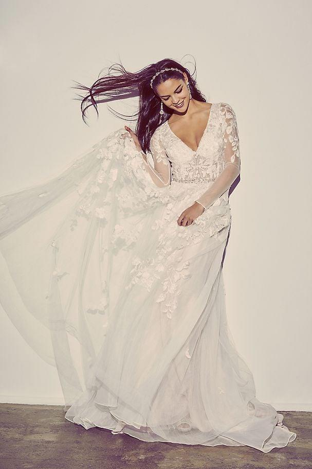 "<p>We have heart eyes for this <a href=""https://www.popsugar.com/buy/Illusion-Sleeve-Plunging-Ball-Gown-Wedding-Dress-582294?p_name=Illusion%20Sleeve%20Plunging%20Ball%20Gown%20Wedding%20Dress&retailer=davidsbridal.com&pid=582294&price=1%2C259&evar1=fab%3Aus&evar9=47551973&evar98=https%3A%2F%2Fwww.popsugar.com%2Fphoto-gallery%2F47551973%2Fimage%2F47552347%2FIllusion-Sleeve-Plunging-Ball-Gown-Wedding-Dress&list1=shopping%2Cwedding%2Cbride%2Cwedding%20dresses%2Cfashion%20shopping%2Cbest%20of%202020&prop13=api&pdata=1"" rel=""nofollow"" data-shoppable-link=""1"" target=""_blank"" class=""ga-track"" data-ga-category=""Related"" data-ga-label=""https://www.davidsbridal.com/Product_illusion-sleeve-plunging-ball-gown-wedding-dress-swg820_all-wedding-dresses"" data-ga-action=""In-Line Links"">Illusion Sleeve Plunging Ball Gown Wedding Dress </a> ($1,259).</p>"