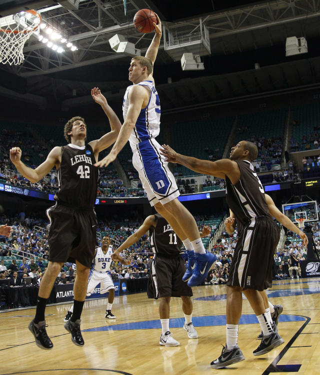 Duke's Mason Plumlee (5) goes up to dunk as Lehigh's Gabe Knutson (42) and C.J. McCollum (3) defend during the first half of an NCAA tournament second-round college basketball game in Greensboro, N.C., Friday, March 16, 2012. (AP Photo/Gerry Broome)