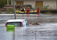 Rescue workers pulling a boat along, wade on a flooded street at San Gavino Monreale in Sardina island November 18, 2013. REUTERS/Rosaspress