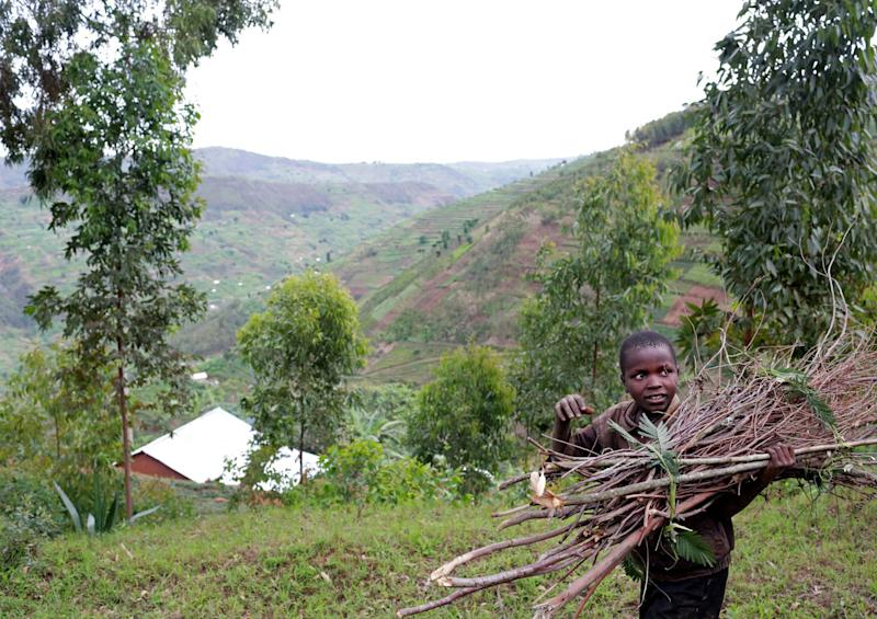A child carries wooden sticks by a road snaking through Mount Kigali, Rwanda on November 15, 2017. (Photograph by Yana Paskova)