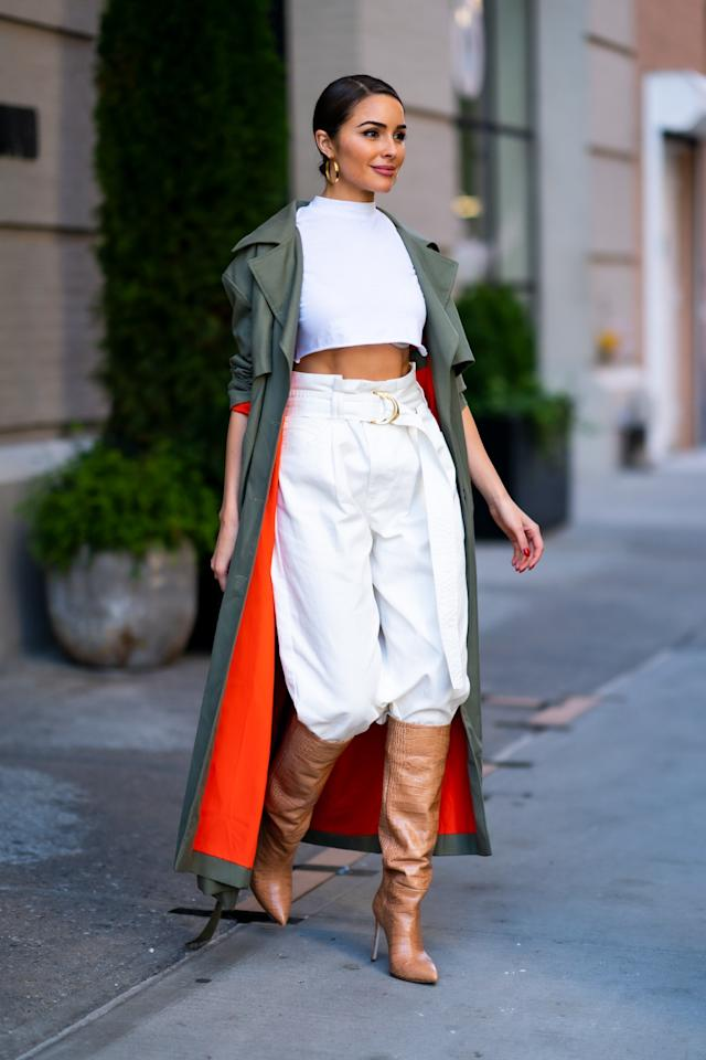 Culpo's belted pleated white trousers are core to this outfit, and she pushes them into a camel boot and finishes with a long army green trench. Chic!
