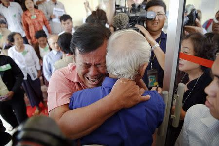 Soum Rithy (C), who lost his father and three siblings during the Khmer Rouge regime, breaks out in tears and hugs another survivor after the verdict was delivered in the trial of former Khmer Rouge head of state Khieu Samphan and former Khmer Rouge leader ''Brother Number Two'' Nuon Chea at the Extraordinary Chambers in the Courts of Cambodia (ECCC) on the outskirts Phnom Penh August 7, 2014. REUTERS/Damir Sagolj