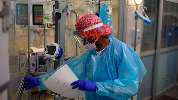 PHOTO: Registered respiratory therapist Niticia Mpanga enters a COVID patient room at the ICU at Oakbend Medical Center in Richmond, Texas, on July 15, 2020. (Mark Felix / AFP via Getty Images)