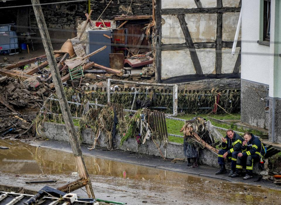 Firefighters rest next to debris of houses in Schuld, Germany, Friday, July 16, 2021. Two days before the Ahr river went over the banks after strong rain falls causing severals deaths and hundreds of people missing. (AP Photo/Michael Probst)