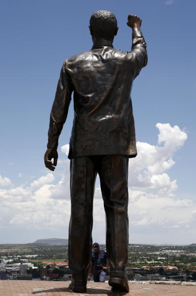 People walk next to a giant statue of former South African President Nelson Mandela on Naval Hill, overlooking the city of Bloemfontein, South Africa, on Wednesday, Dec. 19, 2012. The 94-year old anti-apartheid icon Nelson Mandela is spending a twelfth day in a South African hospital after being diagnosed with a lung infection and undergoing gallstone surgery.(AP Photo/Themba Hadebe)