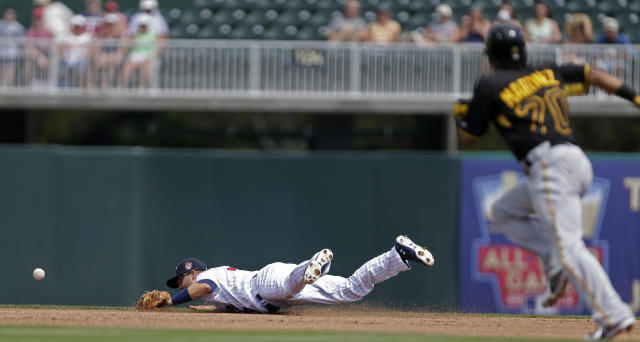 Minnesota Twins second baseman Brian Dozier dives for a grounder single as Pittsburgh Pirates shortstop Michael Martinez advances to second in the first inning of an exhibition baseball game in Fort Myers, Fla., Wednesday, March 12, 2014. (AP Photo/Gerald Herbert)