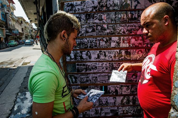 A man buys compact discs at a private stall in Havana, on September 25, 2014 (AFP Photo/Yamil Lage)
