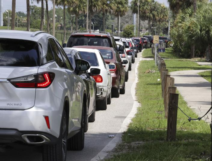 Cars wait in line for COVID-19 testing at Barnett Park, in Orlando, Fla., Thursday, July 29, 2021. The line stretched through the park for more than a mile to the entrance to the Central Florida Fairgrounds. Orange County is under a state of emergency as coronavirus infections skyrocket in Central Florida. The Barnett Park site is testing 1,000 people a day and has closed early in recent days due to reaching capacity. (Joe Burbank/Orlando Sentinel via AP)
