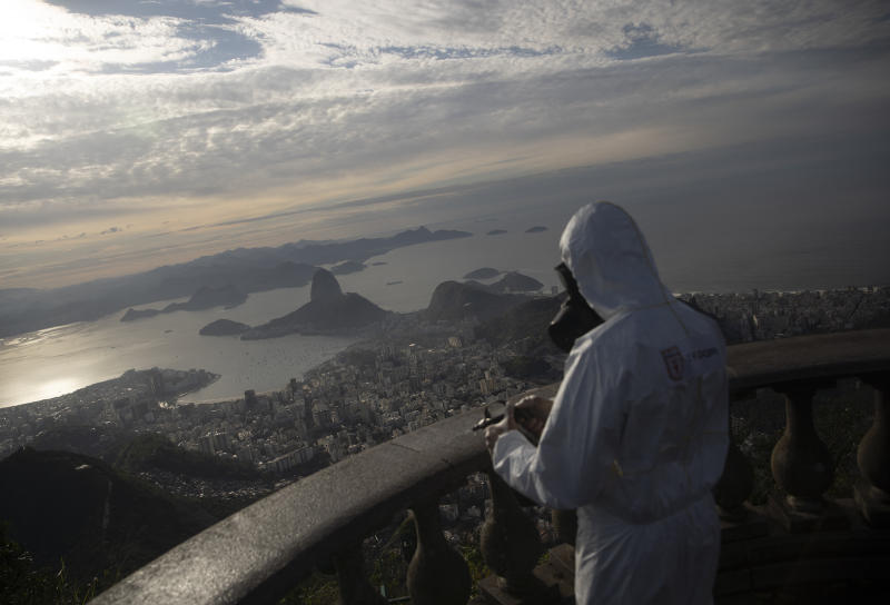 Rio de Janeiro stands below a soldier disinfecting the Christ the Redeemer site, currently closed, during preparations for what tourism officials hope will be a surge in visitors in the upcoming weekend as health restrictions are eased during the new coronavirus pandemic in Rio de Janeiro, Brazil, Thursday, Aug. 13, 2020. (AP Photo/Silvia Izquierdo)