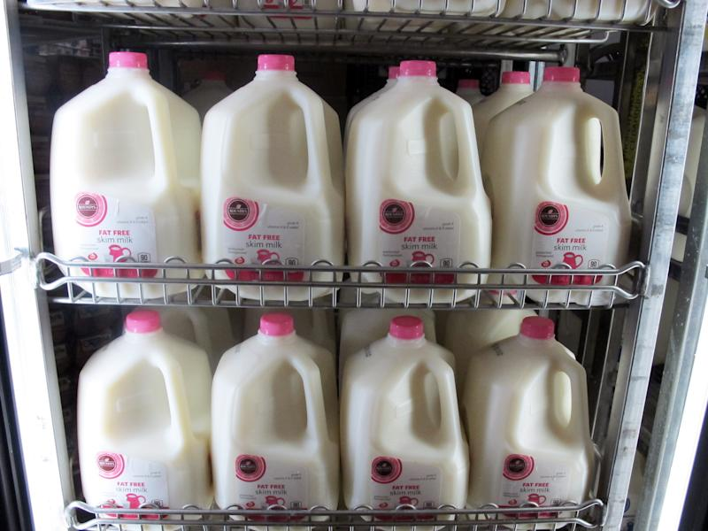 """FILE - In this Dec. 4, 2012 file photo gallons of milk are arranged at a Milwaukee grocery store. As the nation inches toward the economic """"fiscal cliff,"""" anxiety is growing in farm country about a separate looming deadline, one that reaches into the dairy industry and, indirectly, into the household budgets of consumers who buy milk and cheese. (AP Photo/Dinesh Ramde, File)"""