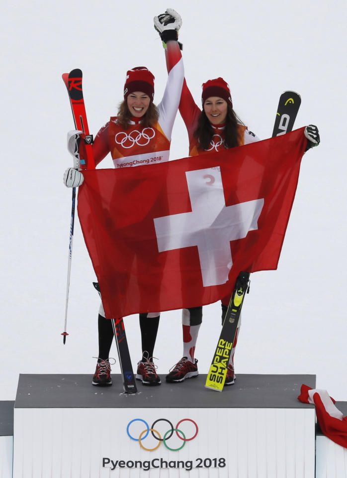 Alpine Skiing - Pyeongchang 2018 Winter Olympics - Women's Alpine Combined - Jeongseon Alpine Centre - Pyeongchang, South Korea - February 22, 2018 -  Gold medallist Michelle Gisin of Switzerland and bronze medallist Wendy Holdener of Switzerland hold a Swiss flag during the victory ceremony. REUTERS/Eric Gaillard