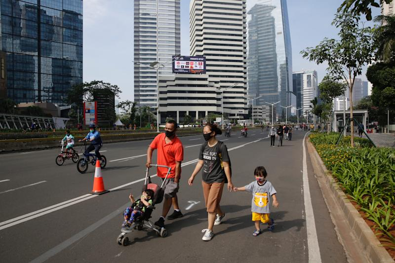 A family walks in the street during a car free day in Jakarta. Source: AAP