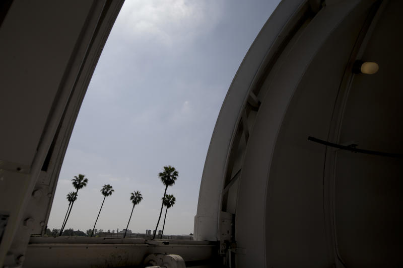 Palm trees are seen through an observatory door at Caltech's Linde + Robinson Laboratory in Pasadena, Calif., Friday, April 12, 2013. A mile above this city, sensors gaze down on the basin from atop Mount Wilson the way a satellite fixates on Earth, collecting pieces of information about Los Angeles' carbon footprint. (AP Photo/Jae C. Hong)