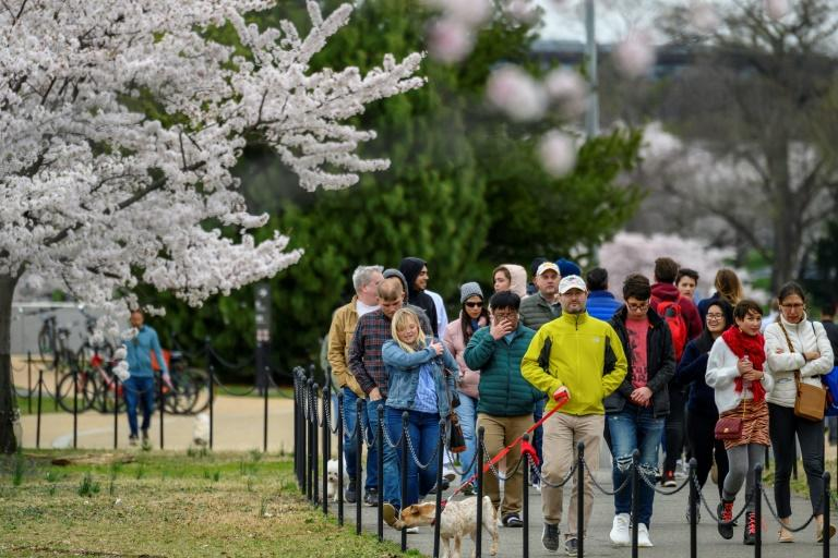 Visitors walk along the Tidal Basin on March 21 as the National Park Service announced traffic controls and closed parking in an attempt to prevent crowding
