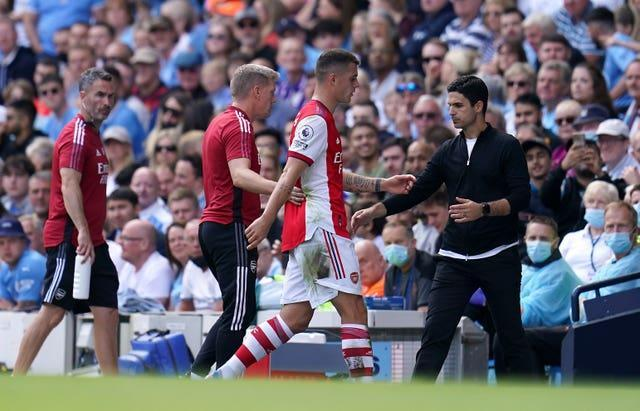 Arsenal's Granit Xhaka walks past beleaguered manager Mikel Arteta after being sent off at Manchester City