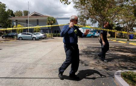 Firefighters cross police tape with the Rehabilitation Center at Hollywood Hills in the background in Hollywood, north of Miami, Florida, U.S. September 13, 2017. REUTERS/Andrew Innerarity
