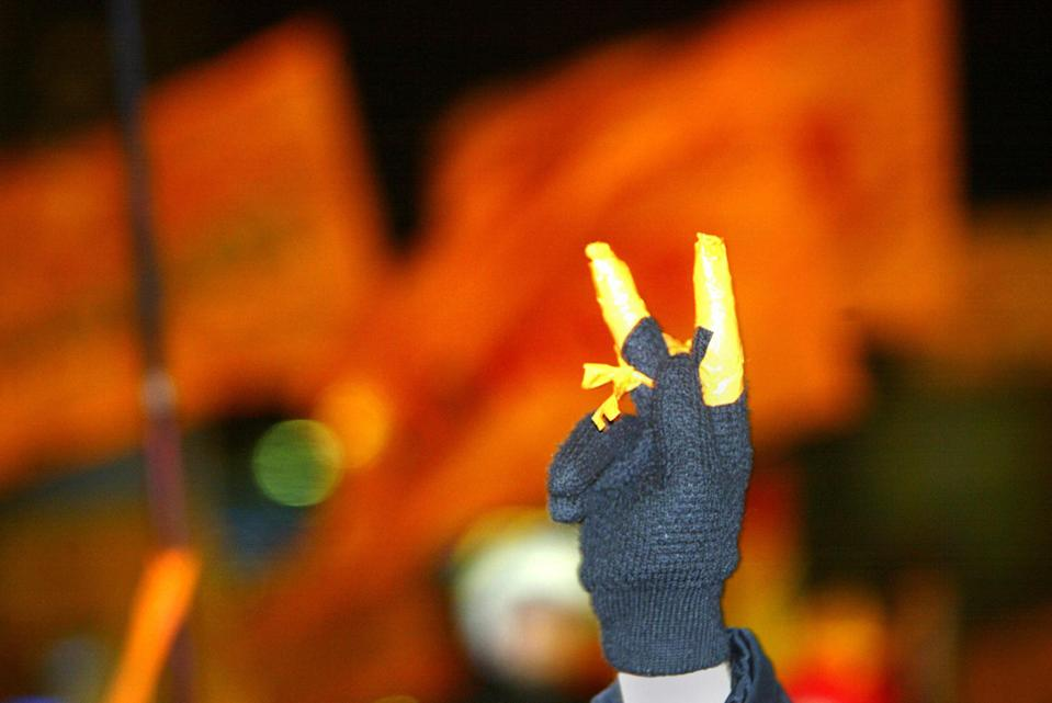 """A supporter of Ukraine's opposition leader Viktor Yushchenko shows a V-sign during a mass rally marking the one-month anniversary of the """"orange revolution"""" in Kiev's central Independence Square on Dec. 22, 2004. (Sergei Supinsky/AFP via Getty Images)"""