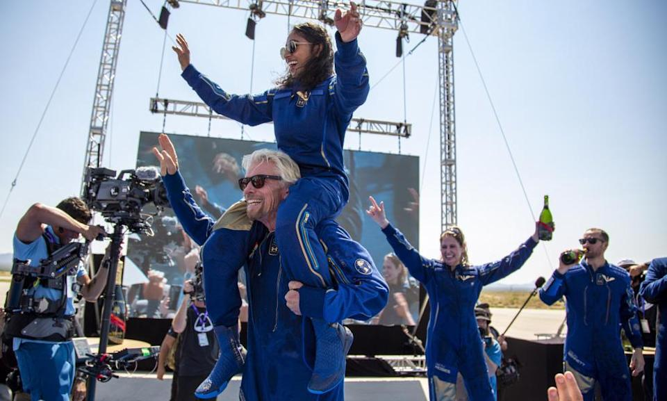 Virgin Galactic founder Richard Branson carries crew member Sirisha Bandla on his shoulders while celebrating their flight to space on 11 July.