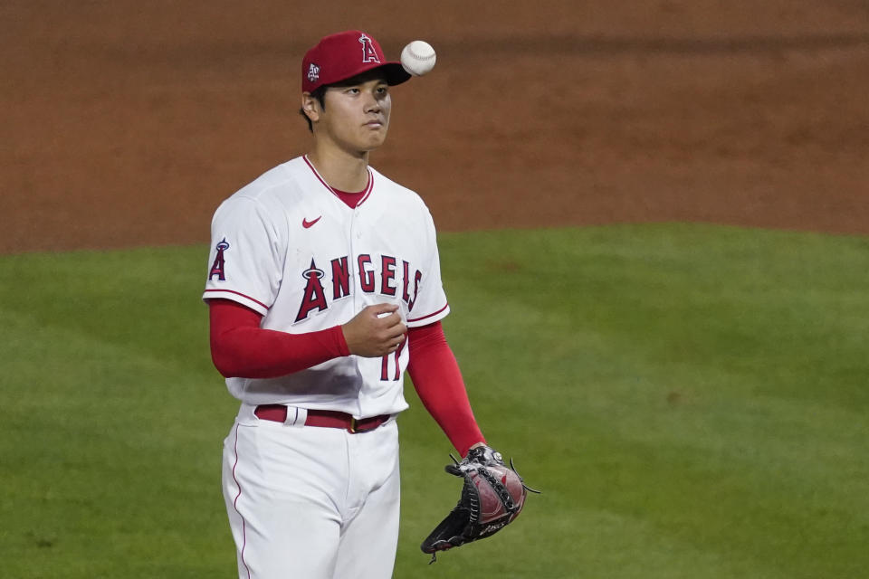 Los Angeles Angels starting pitcher Shohei Ohtani (17) tosses a ball in the air on the mound during a baseball game against the Chicago White Sox Sunday, April 4, 2021, in Anaheim, Calif. (AP Photo/Ashley Landis)