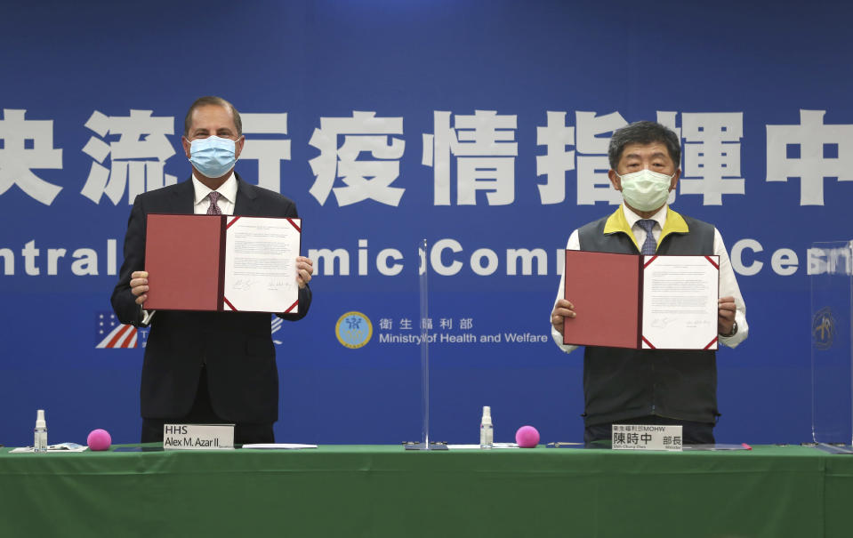 U.S. Health and Human Services Secretary Alex Azar, left, and Taiwanese Minister of Health and Welfare Chen Shih-chung pose for a photo during a signing of a memorandum of understanding at the Central Epidemic Command Center in Taipei, Taiwan, Monday, Aug. 10, 2020. Azar arrived in Taiwan on Sunday in the highest-level visit by an American Cabinet official since the break in formal diplomatic relations between Washington and Taipei in 1979. (AP Photo/Chiang Ying-ying)