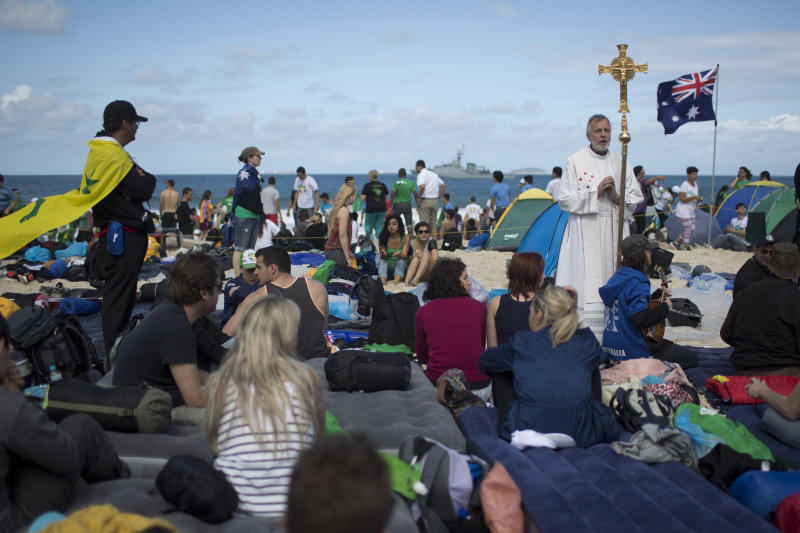 A priest from Australia, top right, gives noon prayer on Copacabana beach as pilgrims wait for a night vigil service with Pope Francis for World Youth Day in Rio de Janeiro, Brazil, Saturday, July 27, 2013. Francis will preside over an evening vigil service on Copacabana beach that is expected to draw more than 1 million young people. (AP Photo/Felipe Dana)