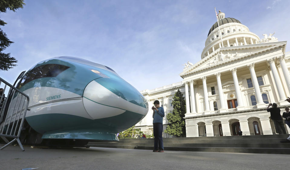FILE — In this Feb. 26, 2015, file photo, a full-scale mock-up of a high-speed train is displayed at the Capitol in Sacramento, Calif. Lawmakers and the Newsom administration are still trying to reach agreement on whether to give the project $4.2 billion that's left in the bond fund voters approved for high-speed rail in 2008. Rail officials say the need it to continue construction beyond next summer, but some state lawmakers want more oversight of the project before releasing it. (AP Photo/Rich Pedroncelli, File)
