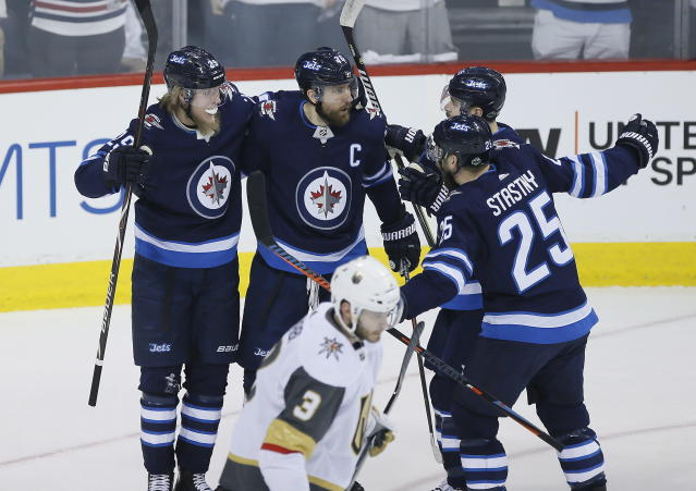Winnipeg Jets' Patrik Laine (29), Blake Wheeler (26), Mark Scheifele (55) and Paul Stastny (25) celebrate Laine's goal against the Vegas Golden Knights during the first period of Game 1 of the NHL hockey playoffs Western Conference final, Saturday, May 12, 2108, in Winnipeg, Manitoba. (John Woods/The Canadian Press via AP)