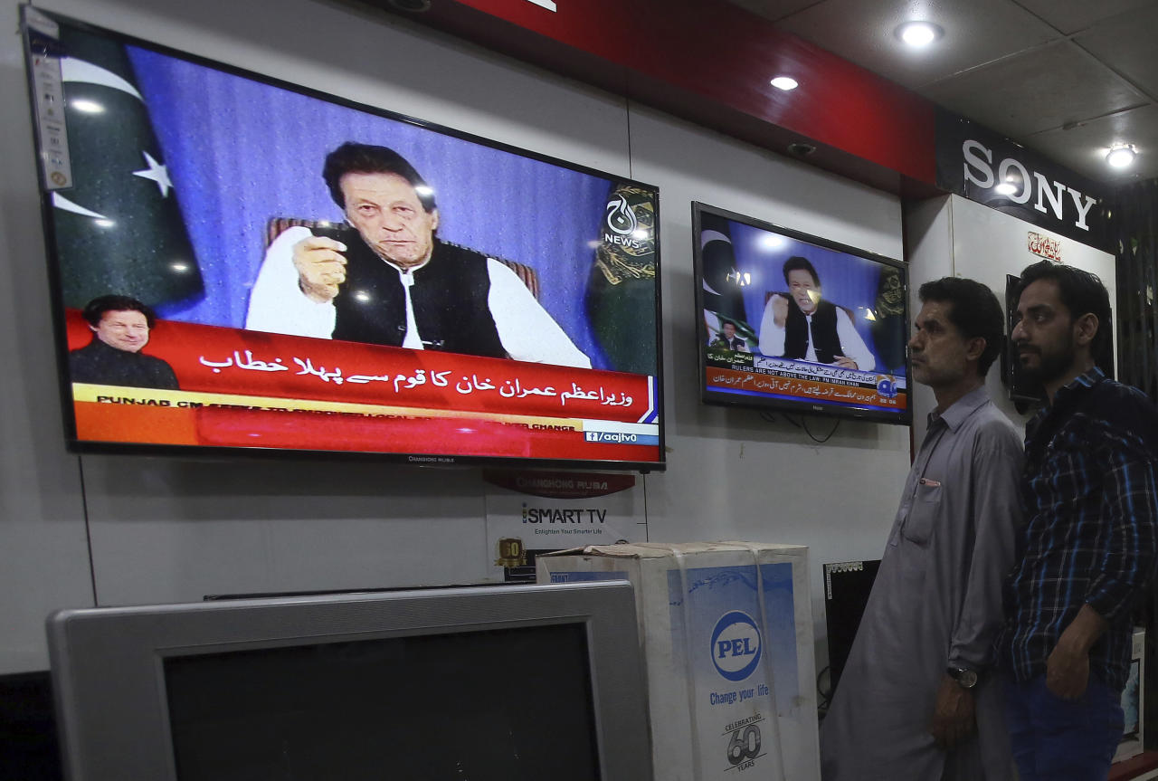 People watch a televised address of Pakistan's newly elected Prime Minister Imran Khan at an electronic shop in Karachi, Pakistan, Sunday, Aug. 19, 2018. Pakistan's newly elected prime minister Imran Khan Sunday said the country was in its worst economic condition and pledged to improve it by adopting austerity to cut government expenditure, introducing progressive taxation, end corruption and bringing back from abroad the plundered public money. (AP Photo/Fareed Khan)