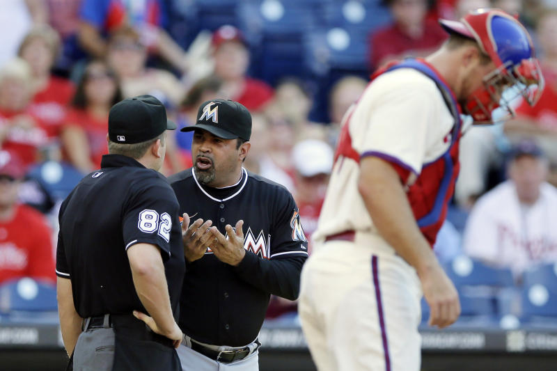 Miami Marlins manager Ozzie Guillen, center, discusses a call with home plate umpire Clint Fagan, left, in the second inning of a baseball game against the Philadelphia Phillies, Wednesday, Sept. 12, 2012, in Philadelphia. At right is Philadelphia catcher Erik Kratz. (AP Photo/Matt Slocum)