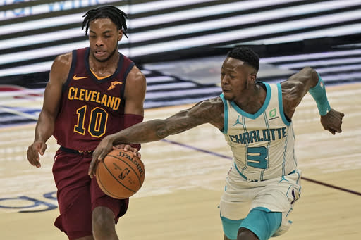 Charlotte Hornets' Caleb Martin (10) tries to steal the ball from Cleveland Cavaliers' Darius Garland (10) during the first half of an NBA basketball game Wednesday, Dec. 23, 2020, in Cleveland. (AP Photo/Tony Dejak)