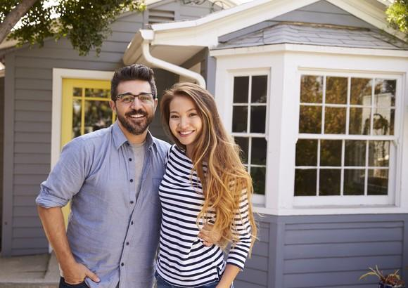 Young man and woman standing in front of a house.