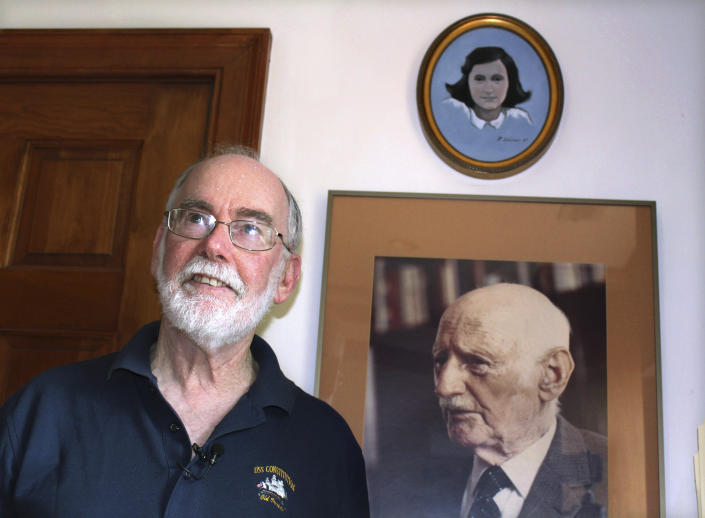 In this June 7, 2019 photo, Ryan Cooper stands next to a photo of Otto Frank, the father of the famed Holocaust victim and diarist Anne Frank, at his home in Yarmouth, Mass. Above the photo is a painting of Anne Frank by Cooper, a local artist who has donated a trove of letters and mementos he received from Otto Frank to the U.S. Holocaust Memorial Museum ahead of the 90th anniversary of Anne Frank's birthday. (AP Photo/Philip Marcelo)
