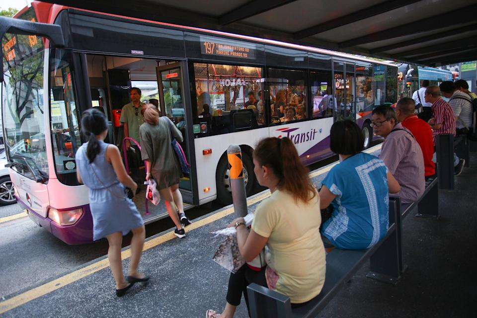 Commuters waiting for buses at a bus stop near Bugis MRT station. (Yahoo News Singapore file photo)