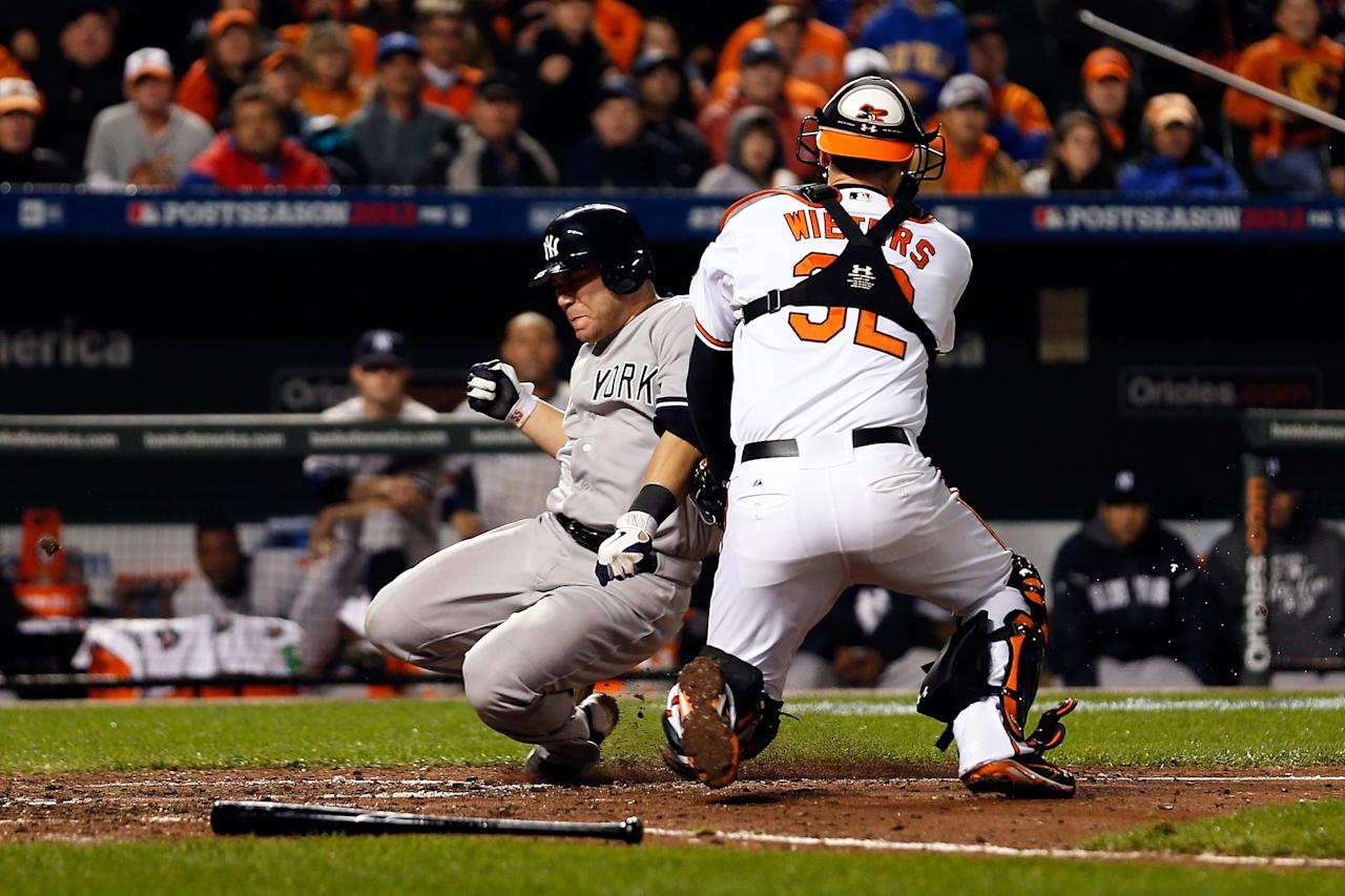 BALTIMORE, MD - OCTOBER 07:  Russell Martin #55 of the New York Yankees is tagged out at home trying to score against Matt Wieters #32 of the Baltimore Orioles in the top of the seventh inning during Game One of the American League Division Series at Oriole Park at Camden Yards on October 7, 2012 in Baltimore, Maryland.  (Photo by Rob Carr/Getty Images)