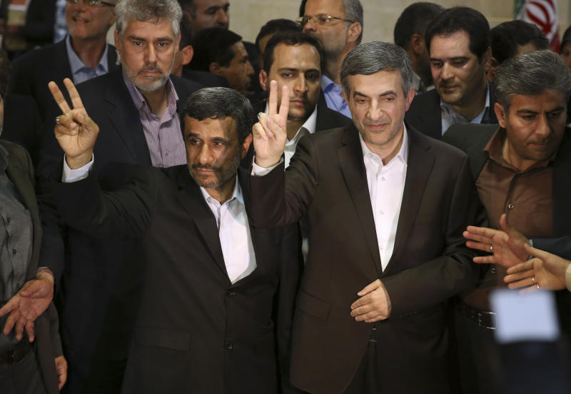 Iranian President Mahmoud Ahmadinejad, left, and his close ally Esfandiar Rahim Mashaei flash victory signs, as they arrive at the election headquarters of the interior ministry for registering of Rahim Mashaei for the upcoming presidential election, in Tehran, Iran, Saturday, May 11, 2013. Iran's powerful former president Akbar Hashemi Rafsanjani has entered the race for the June presidential election. Simultaneously, President Mahmoud Ahmadinejad's close confident Esfandiar Rahim Mashaei also signed up in the last minutes before Saturday's registration deadline. (AP Photo/Ebrahim Noroozi)