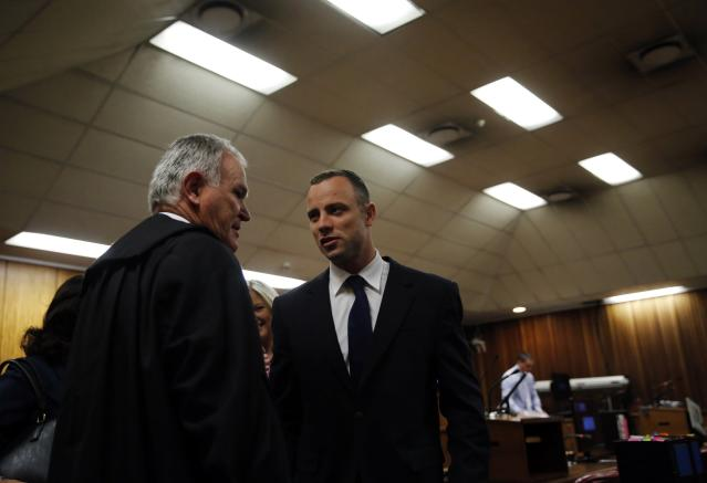 Olympic and Paralympic track star Oscar Pistorius confers with his defence lawyer Barry Roux in the North Gauteng High Court in Pretoria May 6, 2014. Pistorius is on trial for murdering his girlfriend Reeva Steenkamp at his suburban Pretoria home on Valentine's Day last year. REUTERS/Mike Hutchings (SOUTH AFRICA - Tags: SPORT CRIME LAW ATHLETICS)