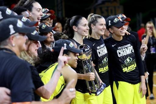 FAIRFAX, VA - SEPTEMBER 12: Members of the Seattle Storm pose with the trophy after defeating the Washington Mystics 98-82 to win the WNBA Finals at EagleBank Arena on September 12, 2018 in Fairfax, Virginia. (Photo by Rob Carr/Getty Images)