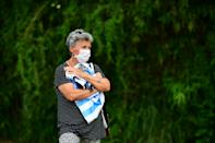 A woman holding a jersey mourns outside the gated community where Argentine football star Diego Maradona's home is located, in Benavidez, Buenos Aires province, where he died on November 25, 2020. (Photo by RONALDO SCHEMIDT / AFP) (Photo by RONALDO SCHEMIDT/AFP via Getty Images)