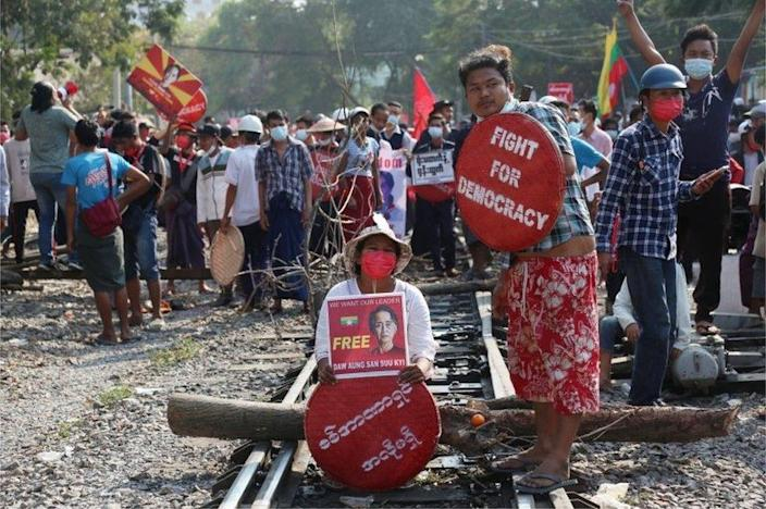 """Demonstrators holding placards calling for the release of detained Myanmar""""s State Counselor Aung San Suu Kyi block railway tracks during a protest against the military coup in Mandalay, Myanmar, 17 February 2021."""
