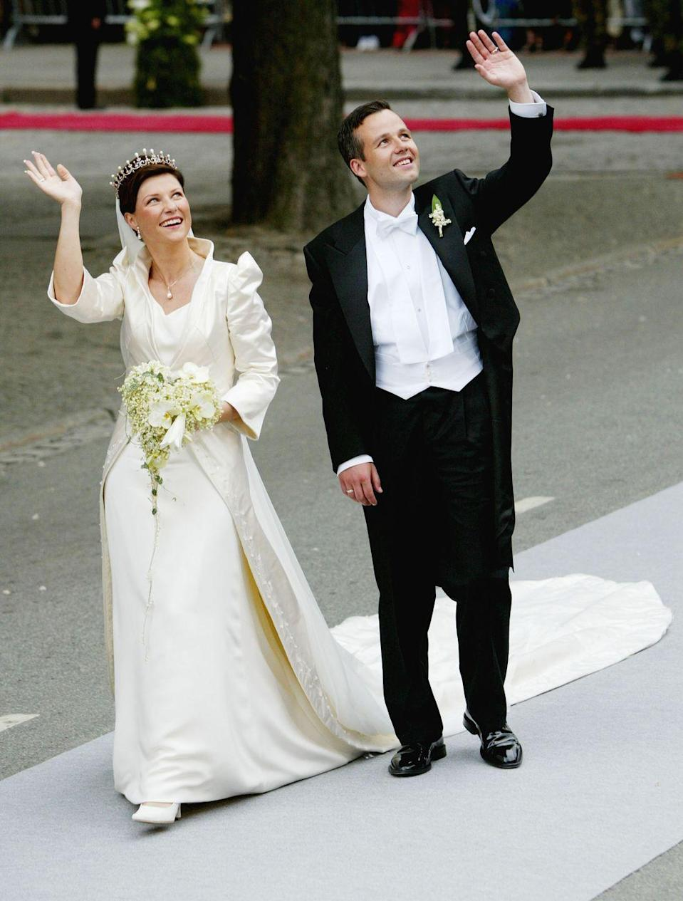 <p>For her 2002 wedding to Ari Behn, the only daughter of the King and Queen of Norway, Princess Märtha-Louise, wore an ivory silk coat dress by Norwegian designer Wenche Lyche over a silk slip dress and the Queen's pearl and diamond tiara. </p>