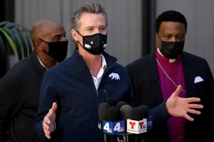 INGLEWOOD, CA - FEBRUARY 21: Governor Gavin Newsom, shown with Steven Bradford (D-Gardena), left, and Rev. Kenneth Ulmer, addresses the media while visiting a mobile COVID-19 vaccination site to discuss the state's efforts to vaccinate hard-to-reach and disproportionately impacted communities at Faithful Central Bible Church on Sunday, Feb. 21, 2021 in Inglewood, CA. State and local agencies vaccinated 250 people from the community on Sunday. (Gary Coronado / Los Angeles Times)