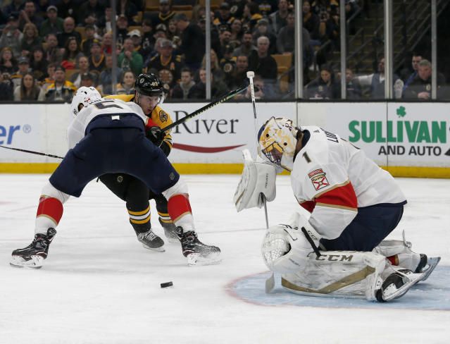 Florida Panthers goaltender Roberto Luongo (1) makes a save as defenseman Aaron Ekblad (5) blocks Boston Bruins left wing Brad Marchand (63) from the puck during the second period of an NHL hockey game, Saturday, March 30, 2019, in Boston. (AP Photo/Mary Schwalm)