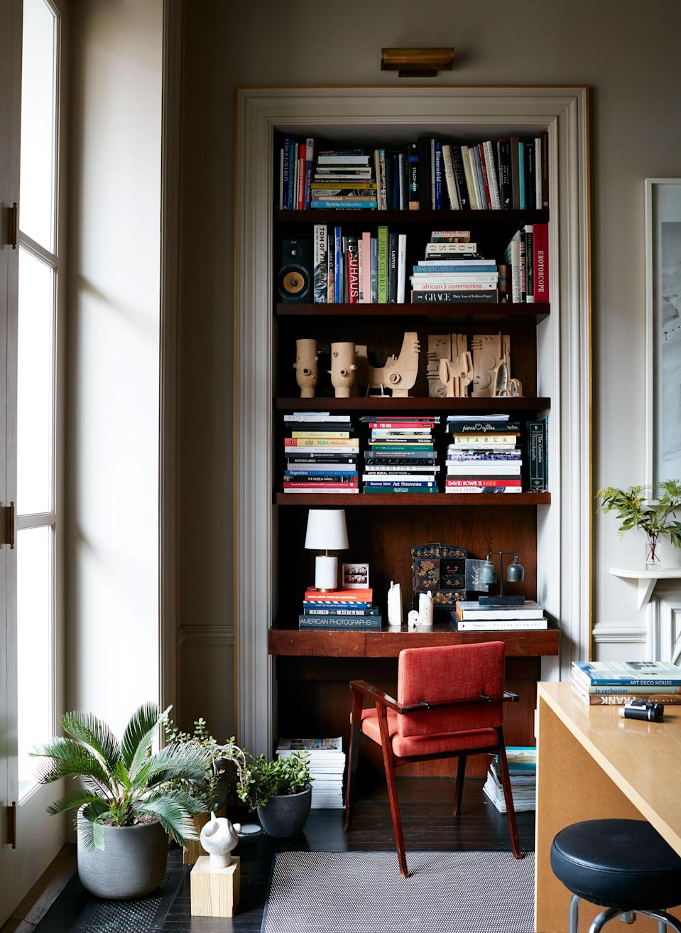 The picture light above the bookcase is a Thomas O'Brien David in brass by Visual Comfort. The study's 1950s rosewood chairs were reupholstered in red-orange linen from Gaston y Daniela at Kravet.