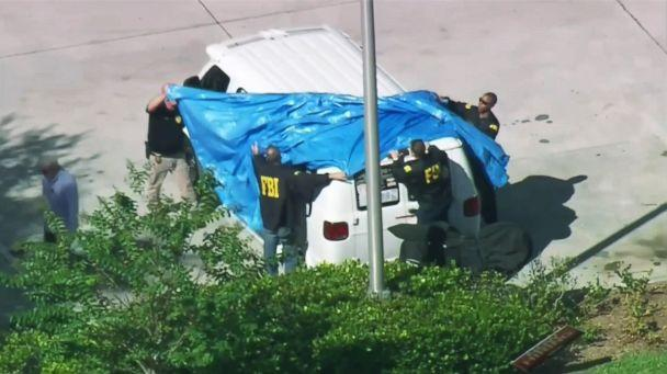 In this frame grab from video provided by WPLG-TV, FBI agents cover a van parked in Plantation, Fla., Oct. 26, 2018, of a suspect in the mass bomb mailings. (WPLG-TV via AP)