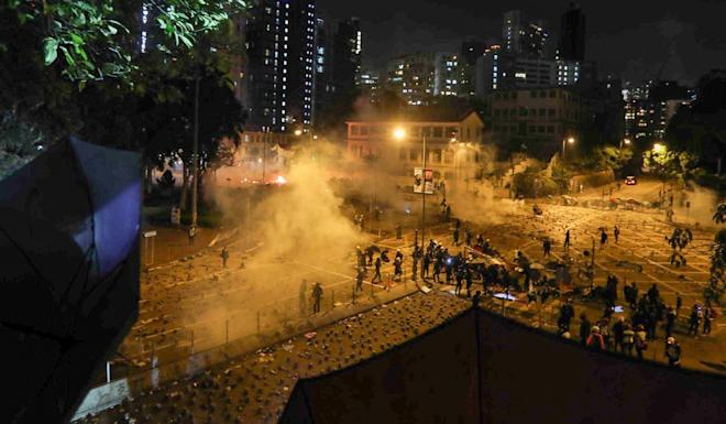 Police fire tear gas at protesters at the intersection of Chatham Road South and Austin Road outside Polytechnic University. Photo: Xiaomei Chen