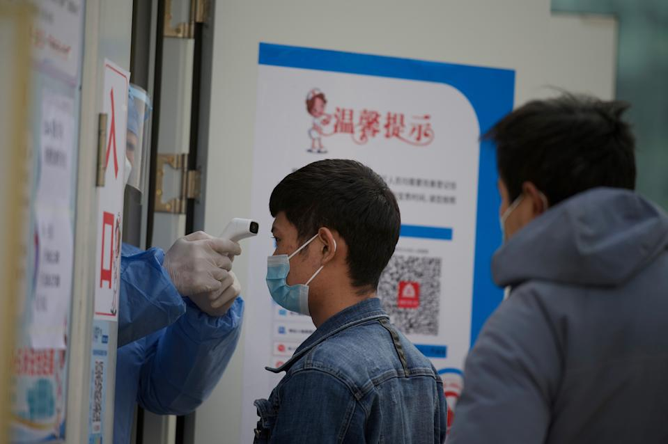 A medical worker checks the temperature of people getting nucleic acid tests at a hospital in the Daxing district of Beijing on January 22, 2021, after a partial lockdown was imposed on the Chinese capital
