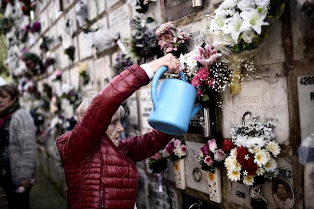 <p>Maria Luisa Mendicote waters flowers on a niche bearing the remains of her parents and a nephew at Derio cemetery on All Saints' Day, near Bilbao, Spain, Nov. 1, 2017. (Photo: Vincent West/Reuters) </p>