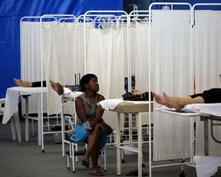 A woman sits next to her relative, who is receiving treatment for dengue symptoms, in a medical tent in Rio Claro, Brazil March 5, 2015. REUTERS/Paulo Whitaker