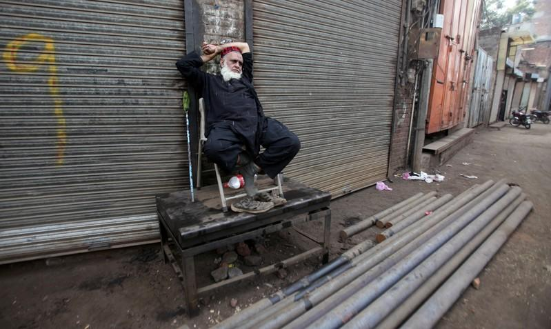 A worker sits outside closed shops during a country-wide lock down by the traders and business community, against what they say is imposition of taxes by the government in Lahore